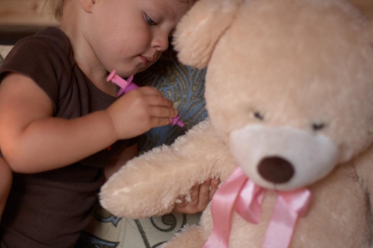 ребёнок делает прививку игрушке