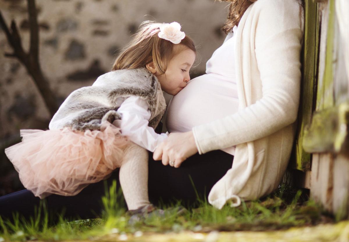 девочка целует живот беременной мамы, как подготовить старшего ребёнка к рождению младшего
