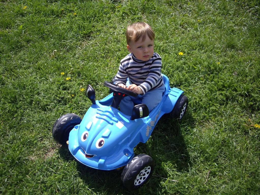 мальчик катается на машинке