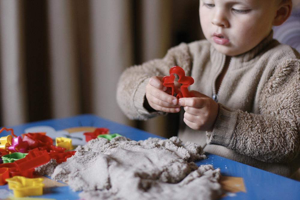 ребёнок играет с кинетическим песком