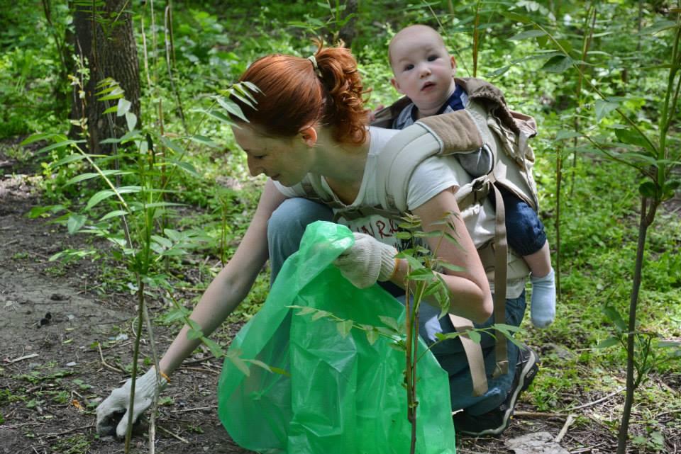 мама убирает мусор с ребёнком в слинге