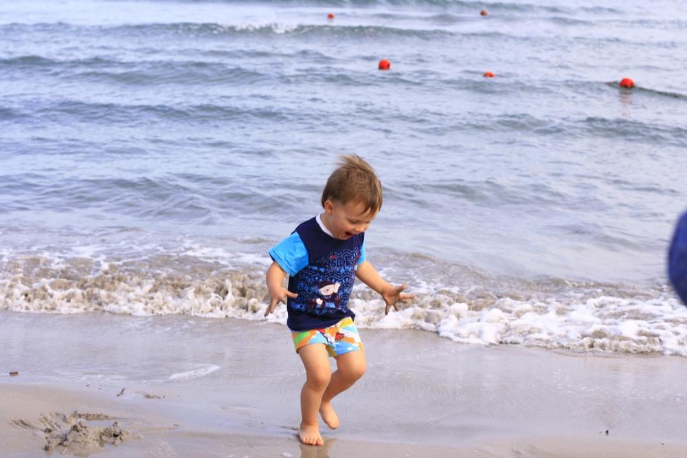 ребёнок играет на берегу моря