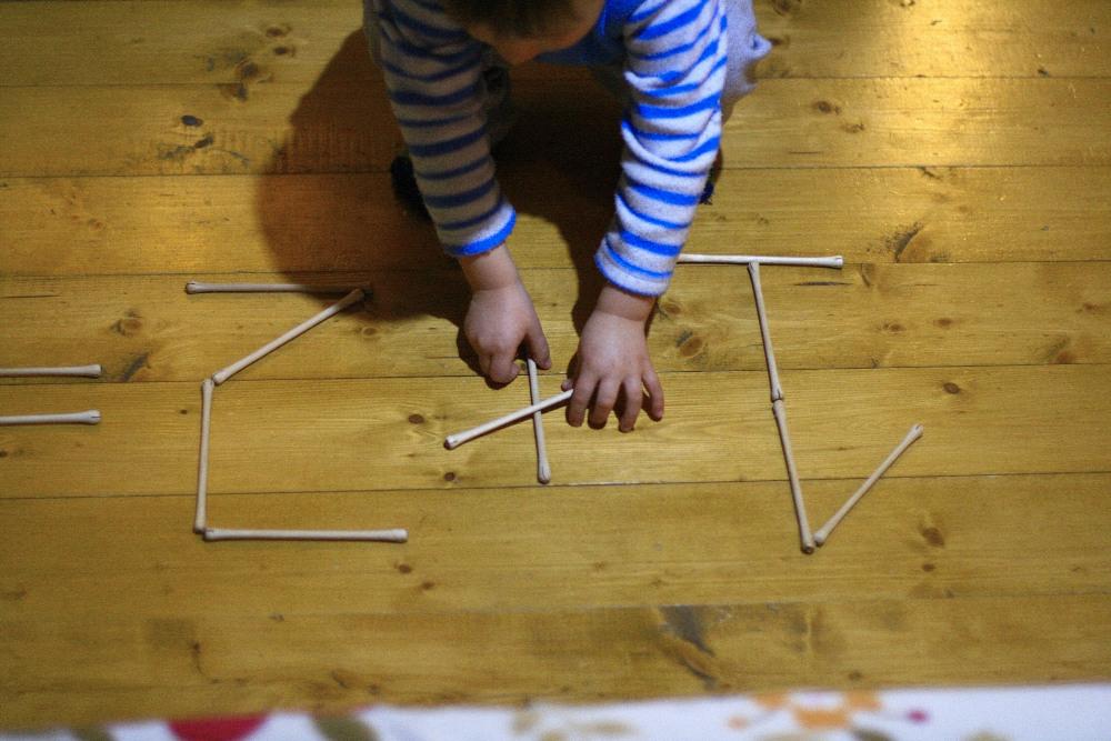 мальчик складывает цифры из палочек